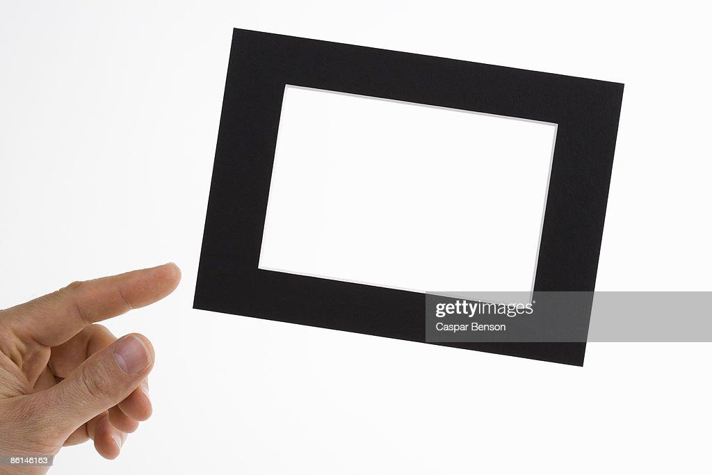 A human hand adjusting a slanted picture frame
