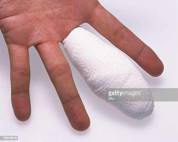Human hand bandaged middle finger