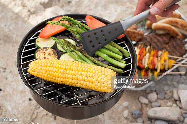 Human hand barbecuing with barbecue tongs, close up