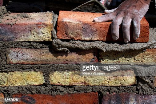 Human hand building brick wall