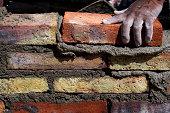 Human hand building brick wall