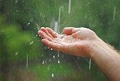 Human hand catching rain drops