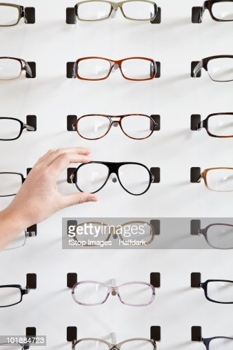 A human hand choosing a pair of glasses in an eyewear store