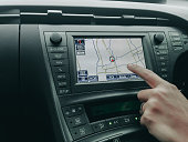 human hand control and point to car moniyor display with GPS navigator with interior design in luxury car