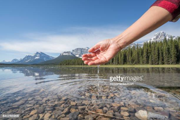 Human hand cupped to catch fresh water from mountain lake