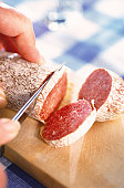 Human hand cutting smoked salami on chopping board