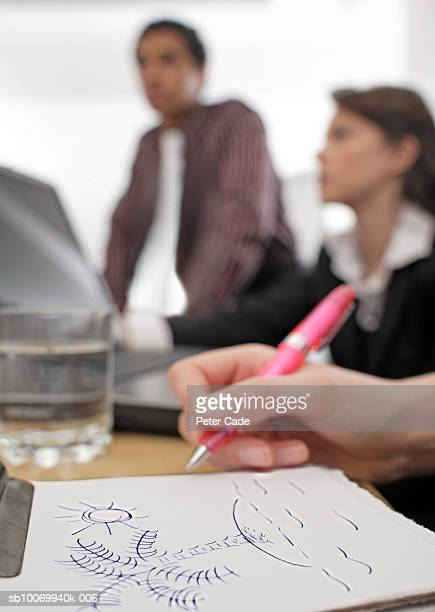 Human hand drawing palm tree on paper, businesspeople in background