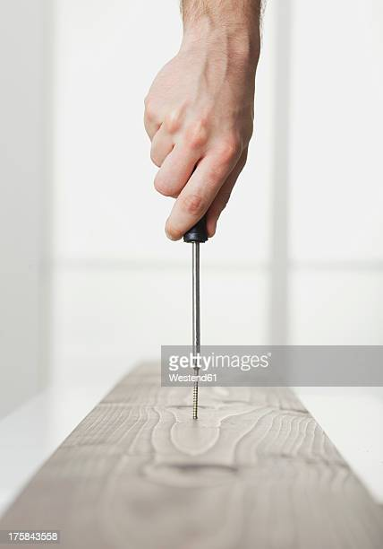 Human hand driving screw into wooden board