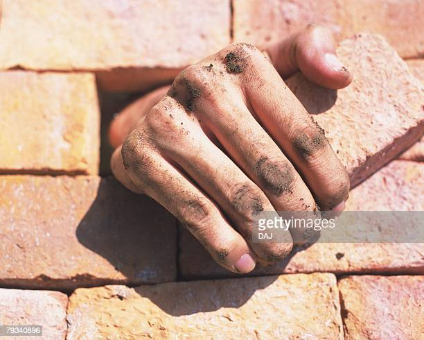Human hand getting out of brick wall