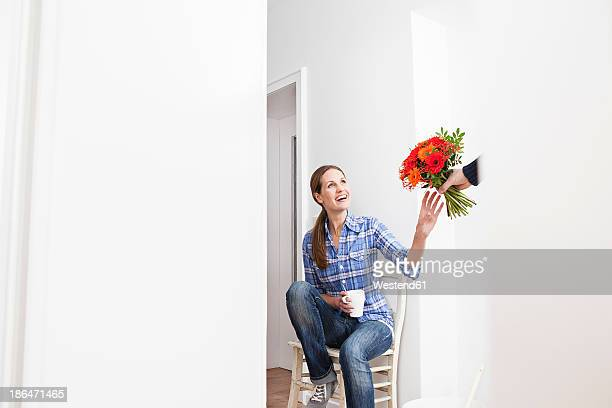 Human hand giving bunch of flowers to woman, smiling