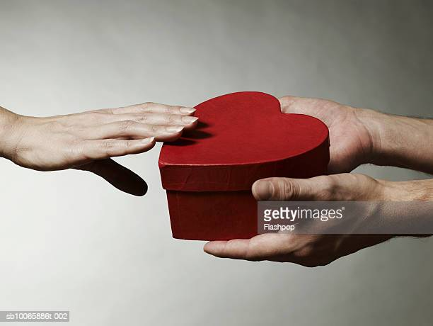 Human hand  giving heart shaped box to other