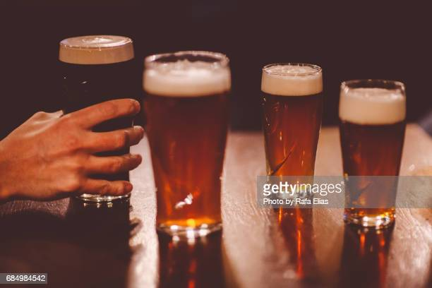 Human hand grabbing pint of stout between some others pints of beer