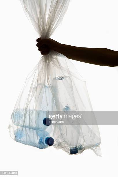 A human hand holding a transparent garbage bag of plastic bottles