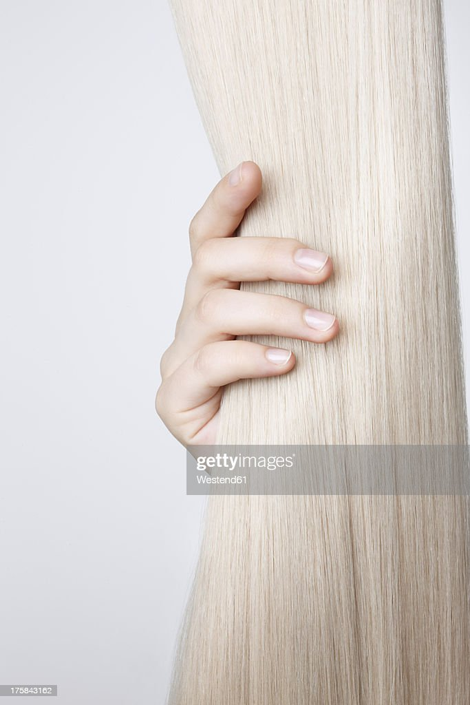 Human hand holding blond hair against white background, close up : Stock Photo