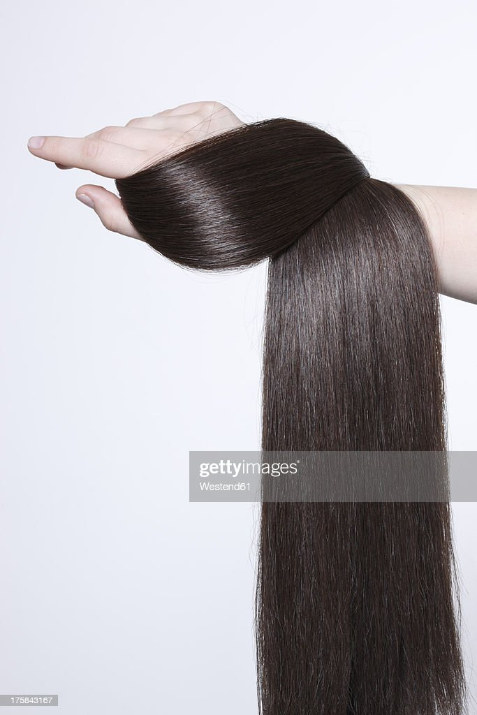 Human hand holding brown hair against white background, close up