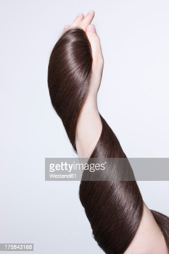 Human hand holding brown hair against white background, close up : Stock Photo
