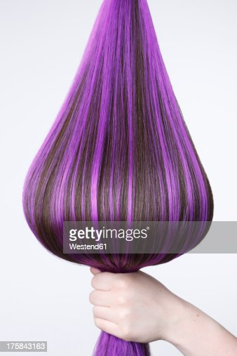 Human hand holding brown hair with purple highlights against white background, close up