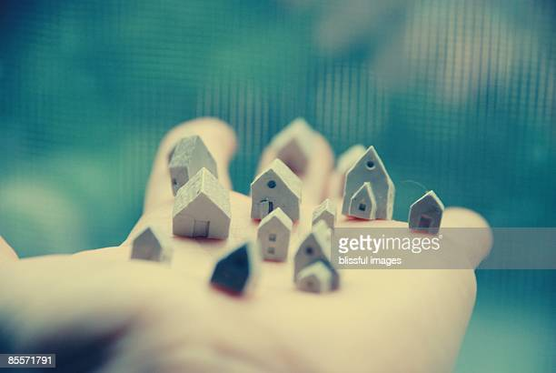 Human hand holding doll's house