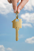 Close up of human hand holding key to a dream house over sky background