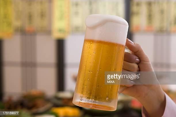 Human Hand Holding Jug of Beer at Izakaya