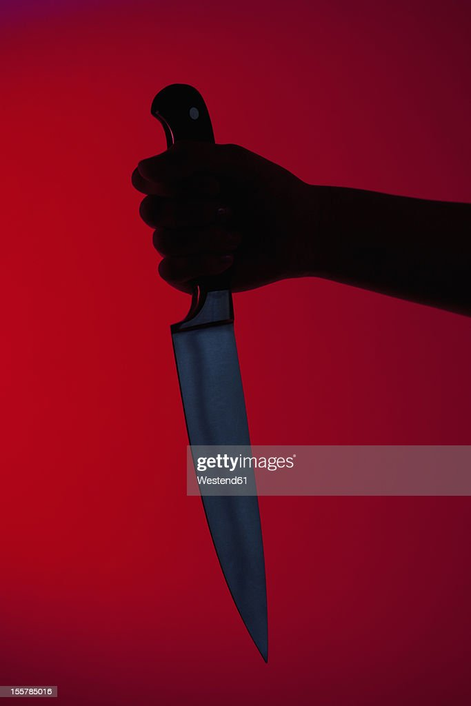 Human hand holding kitchen knife against red background : Stock Photo