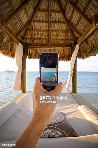Human hand holding Mobile phone in a beachfront cabana, Jamaica, Caribbean