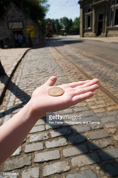 Human hand holding penny