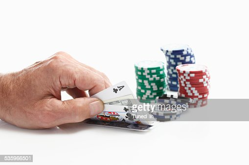Human hand holding playing cards with gambling chips : Stock Photo