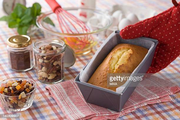 Human Hand Holding Pound Cake in Mold