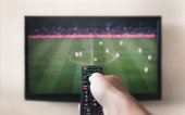 Human hand holding remote control at TV screen