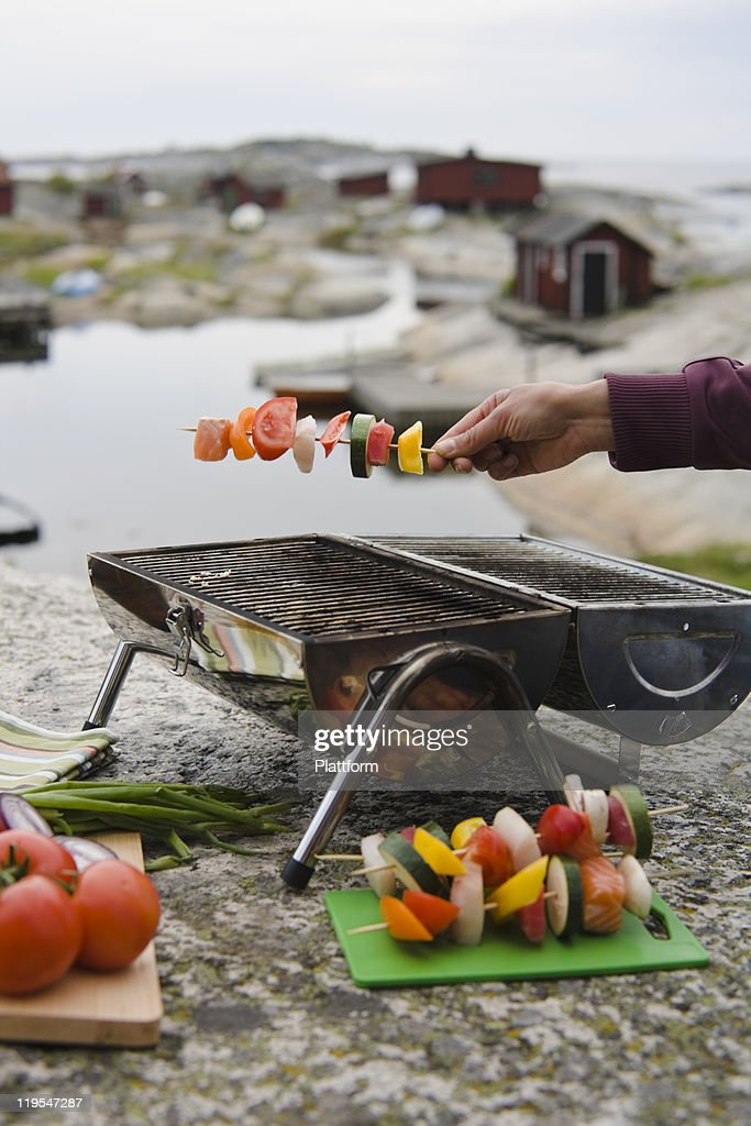 Human hand holding skewer with vegetable over grill : Stock Photo
