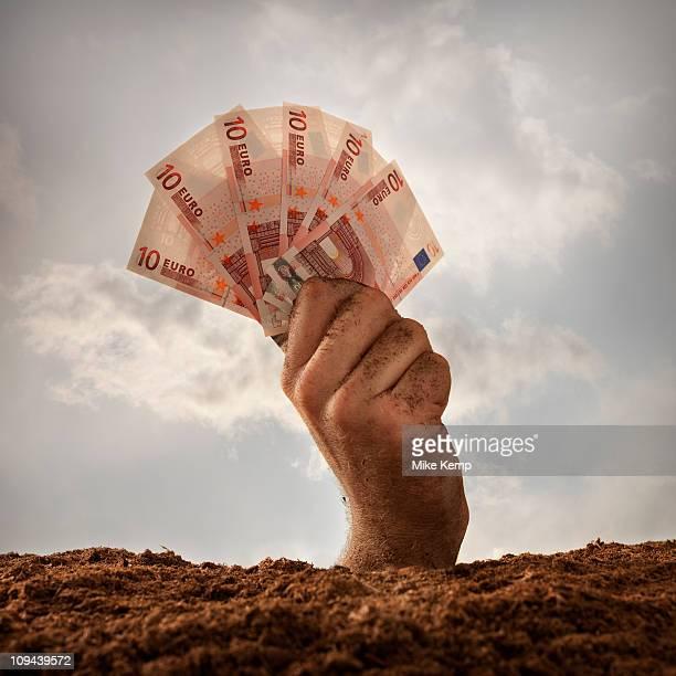 Human hand holding ten euros banknotes, studio shot