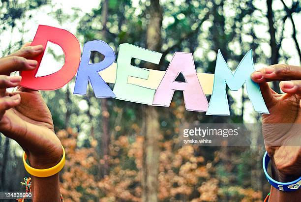 Human hand holding text 'Dream' made from paper.