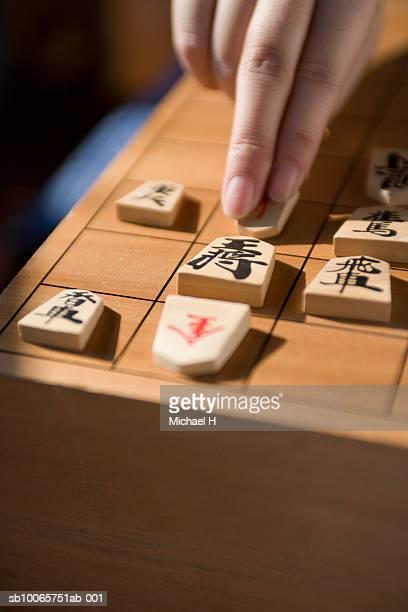 Human hand moving koma on shogi board