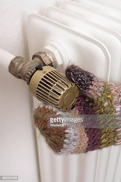 Human hand on heating regulator, close-up