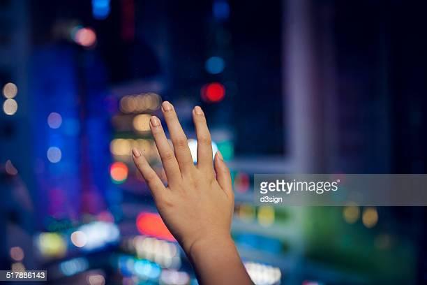 Human hand on window overlooking city at night