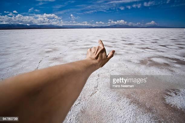 Human hand pointing towards a salt flat, San Salvador de Jujuy, Jujuy Province, Argentina