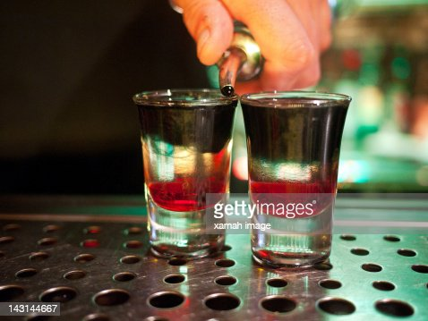 Human hand pouring liquor in glass : Stock Photo