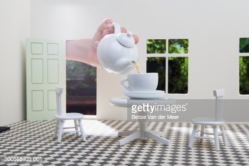 Human hand pouring tea in teacup on table in dolls house, close-up : Stock Photo