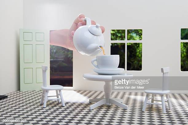 Human hand pouring tea in teacup on table in dolls house, close-up