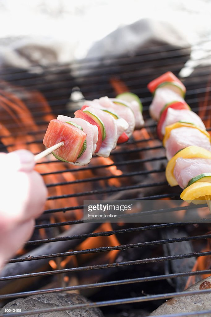 Human hand preparing kebabs on barbecue grill rack, close up : Stock Photo