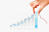 Human hand pulling graph bar suggesting increase of sales or business