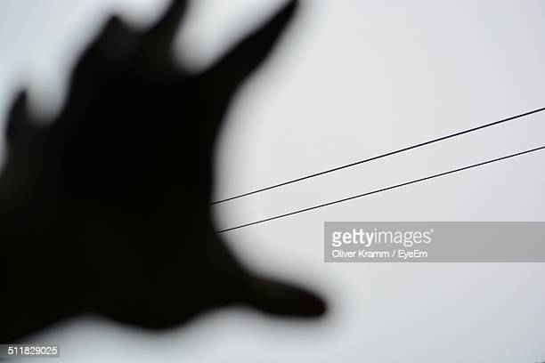 Human hand reaching towards power cable