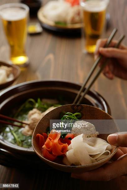 Human hand serving dumpling in bowl, close-up