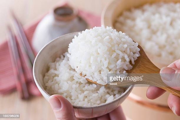 Human Hand Serving Steamed Rice into Rice Bowl