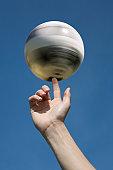 A human hand spinning a soccer ball on a human finger