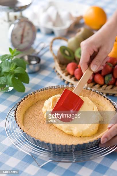 Human Hand Spreading Custard on Tart