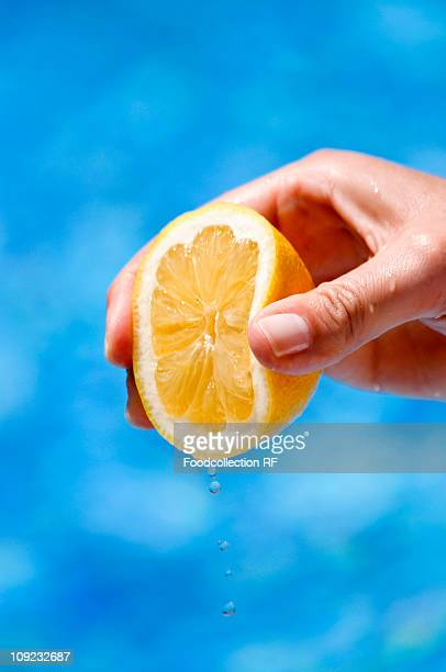 Human hand squeezing lemon, close-up