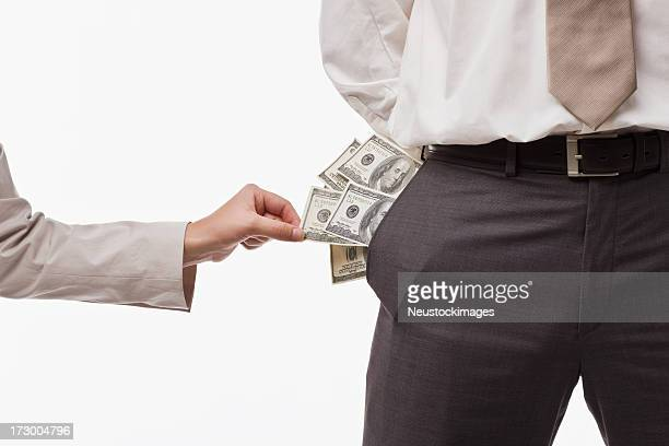 Human hand taking money from businessman's pocket
