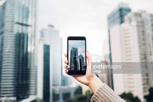 Human hand taking picture with cell phone of downtown modern skyscrapers